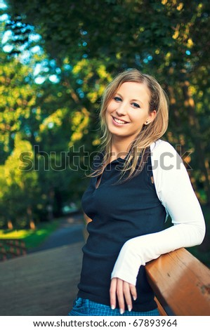 Beautiful young woman standing on a moat in park in autumn - stock photo