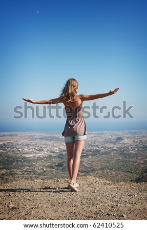 beautiful young woman standing on a mountain top with outstretched arms - stock photo