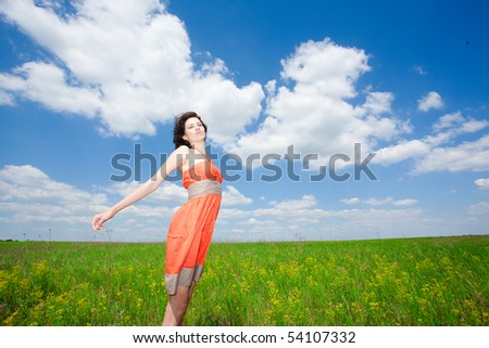 Beautiful young woman standing on field enjoying wind wave; looking at camera - stock photo