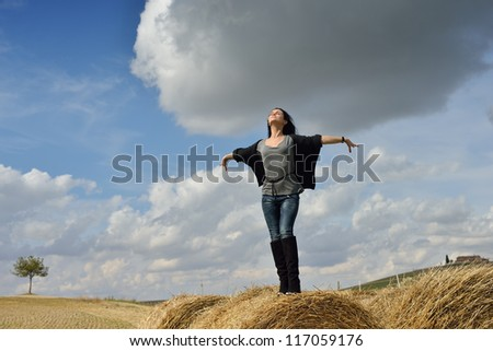 Beautiful young woman standing on stack of hay on stormy day in the country, Tuscan, Italy