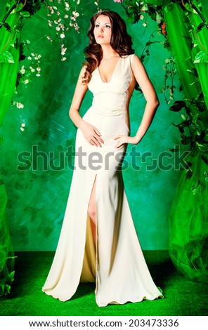 Beautiful young woman standing under an arch of flowers and overgrown loach. Spring and summer beauty. - stock photo