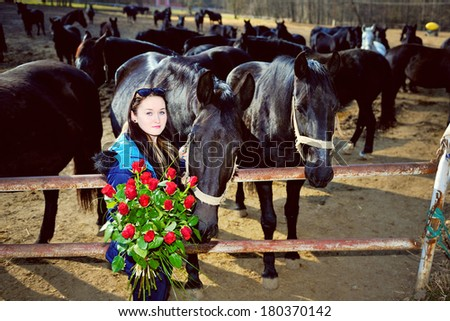 Beautiful young woman standing with bunch of roses before black horses - stock photo