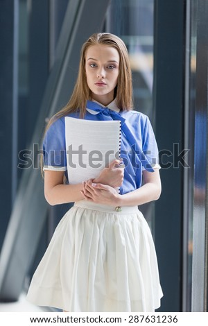 Beautiful young woman standing with notebook paper, looking in the camera. - stock photo