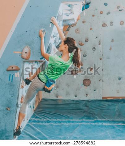 Beautiful young woman starts to climbing wall - stock photo