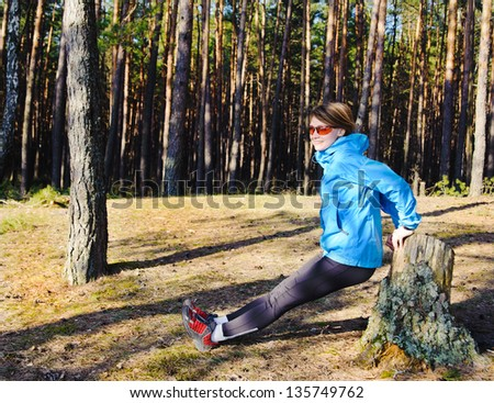 Beautiful young woman stretching in the forrest.