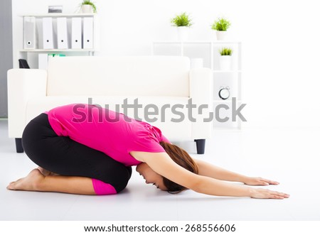 beautiful young woman stretching on the floor  - stock photo