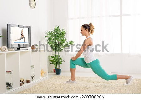 Beautiful young woman stretching out her legs at home in front of the tv - stock photo