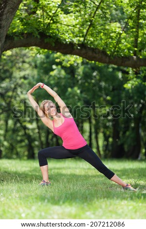 Beautiful young woman stretching outdoors