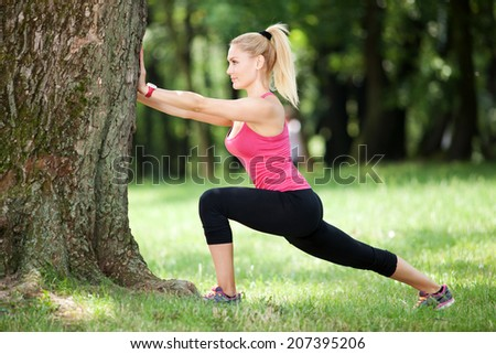 Beautiful young woman stretching outdoors - stock photo