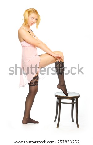 Beautiful young woman stripping down black nylons. - stock photo