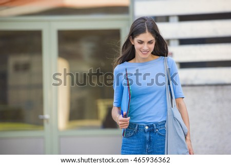 beautiful young woman student is walking out of a university building
