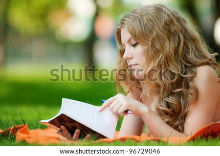 Beautiful young woman study at green summer park