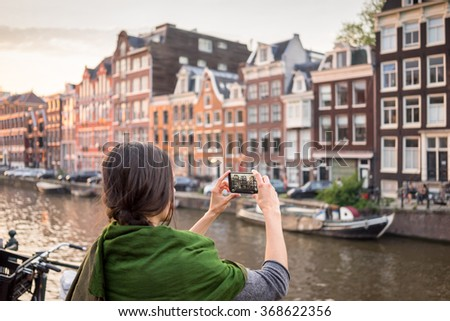 beautiful young woman takes pictures in vacation spent in Amsterdam with beautiful architecture - stock photo