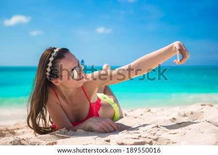 Beautiful young woman taking a photo herself on tropical beach