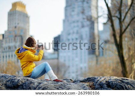 Beautiful young woman taking a photo of skyscrapers while sitting on a rock in Central Park, New York - stock photo