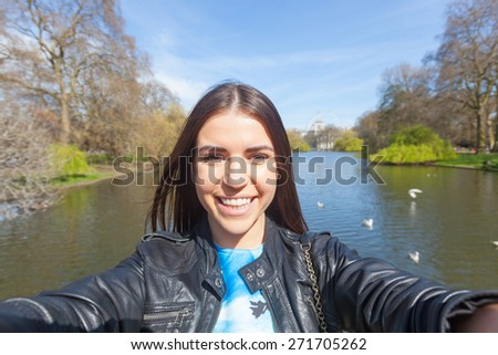 Beautiful young woman taking a selfie in London at St James park with lake and trees on background. She is holding the phone and looking at it. - stock photo
