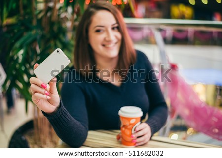 beautiful young woman taking a selfie with a coffee in a cafe