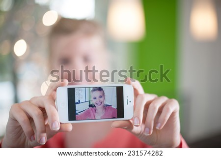 beautiful young woman taking a Selfie with her smartphone, close up on the phone screen - stock photo