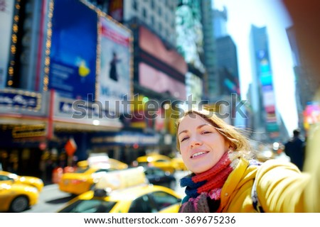 Beautiful young woman taking a selfie with her smartphone on Times Square, New York - stock photo