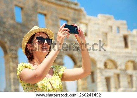 Beautiful Young Woman Taking Photo of Ancient Roman Arena in Pula with Her Smartphone. Travel and Vacation in Croatia. - stock photo