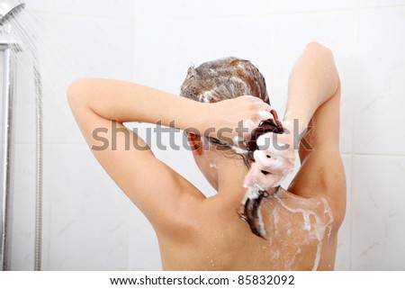 Beautiful young woman taking shower