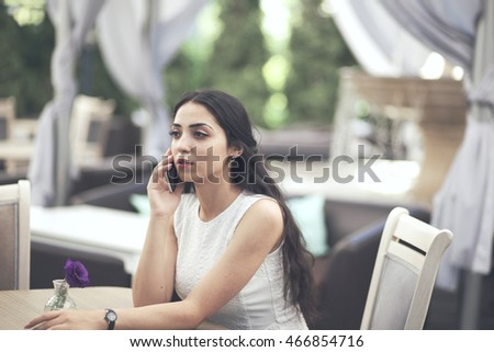 Beautiful young woman talking on her phone in a restaurant
