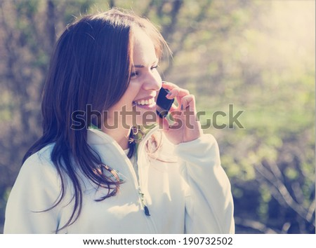 beautiful young woman talking on mobile phone and smiling - stock photo