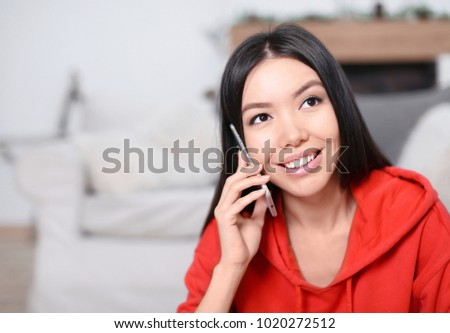 Beautiful young woman talking on mobile phone at home