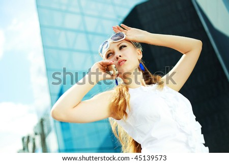 beautiful young woman talking on the cell-phone outdoor - stock photo
