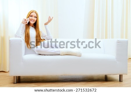 Beautiful young woman talking on the phone at home sitting on the couch. - stock photo