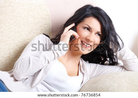 Beautiful young woman talking on the phone laying on the sofa - stock photo