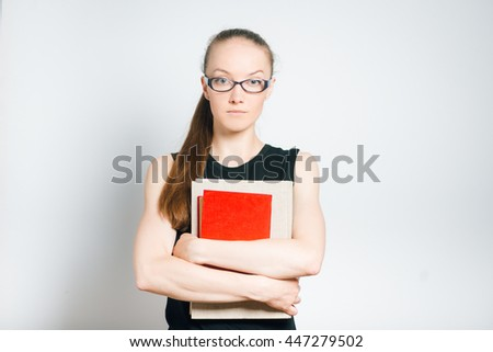 beautiful young woman teacher holding a book in hands, isolated on a gray background - stock photo