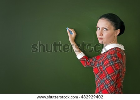 Beautiful young woman teacher in a red striped dress writing with blue chalk  on a green chalkboard