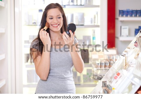 Beautiful young woman testing make up in a drug store - stock photo