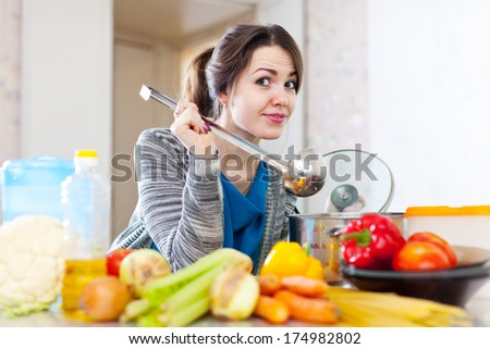 beautiful young woman tests food with ladle in the kitchen  - stock photo