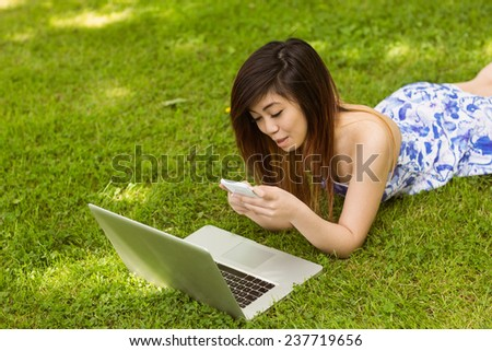 Beautiful young woman text messaging in the park - stock photo