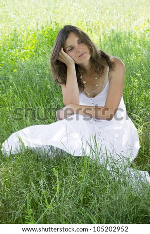 Beautiful young woman thinking about something, sitting in a meadow - stock photo