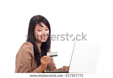 Beautiful young woman thinking to buy online using credit or debit card while holding a laptop isolated on white - stock photo