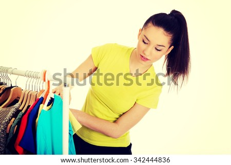 Beautiful young woman thinking what to dress.