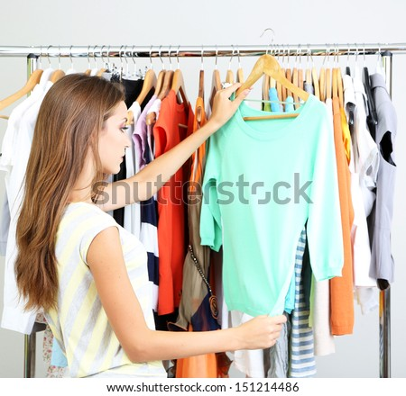 Beautiful young woman  thinking what to dress near rack with hangers