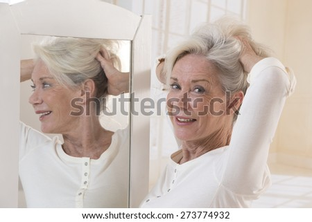 Beautiful young woman touching her hair with hands and smiling while standing in front of the mirror - stock photo