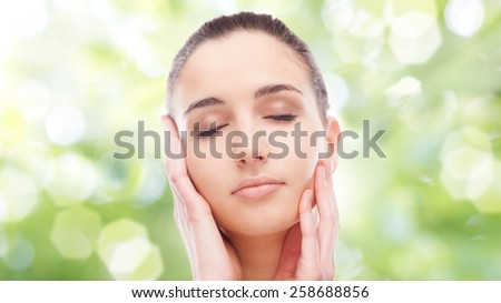 Beautiful young woman touching her radiant face skin with eyes closed on green background - stock photo