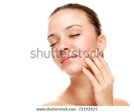 Beautiful young woman touching her skin. Isolated over white. - stock photo