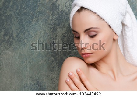 Beautiful young woman touching her soft skin after a beauty treatment - stock photo