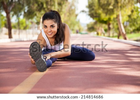 Beautiful young woman touching her toes and stretching at a running track - stock photo