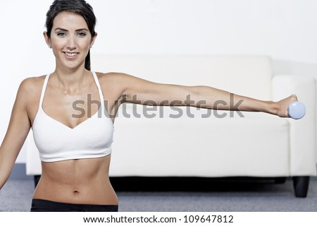 Beautiful young woman training with weights at home - stock photo