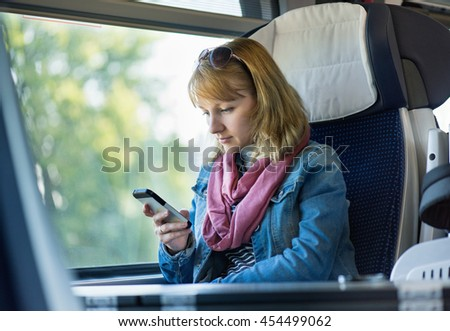 Beautiful young woman traveler in a train or bus, making phone call.