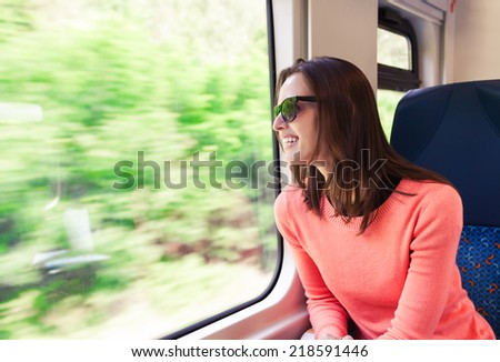 Beautiful young woman traveling by train - stock photo