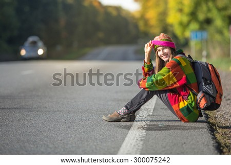 Beautiful young woman traveling sitting on road happy smiling - stock photo