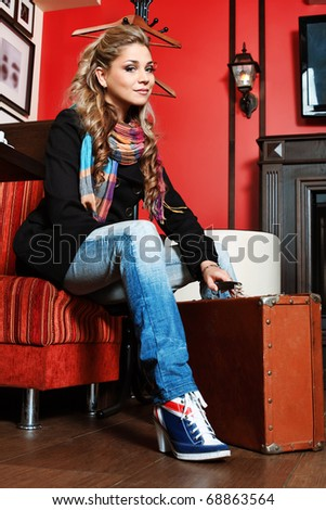Beautiful young woman traveller with an old suitcase at a caf - stock photo